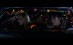 Sarah Polley and Breckin Meyer converse in a car in a still from the film.