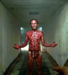 A still from the film showing Epy Kusnandar, wearing only a lioncloth and covered in blood after a great deal of self-mutilation, welcoming the holder of the camera.