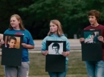 Students stand in a line, holding up the pictures of classmates who have committed suicide because of bullying, in this still from the film.