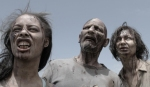 A trio of zombies focuses on a survivor in a still from the film.