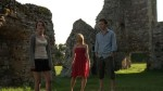 Three of the film's principals wander amoung the ruined walls of a parish house in a still from the film.