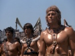 Rick Hill, wearing very little armor, and a couple of other unclad warriors in a still from the film.