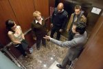 The five principals, trapped in the elevator, in a still from the film.