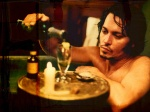 Johnny Depp, in the bath, pouring himself a bit of absinthe in a still from the film.