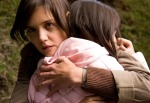 Katie Holmes glares at something offscreen while hugging Bailee Madison in a still from the film.