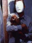 Jason Flemyng, masked, cradles a pooch in a still from the film.