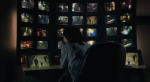 Jackie sits in front of a bank of monitors in a still from the film.