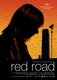 Jackie, shadowed, in the foreground against one of the buildings of Red Road on the movie poster.