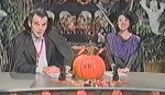 Two news anchors in cheesy Halloween costumes in a still from the film.