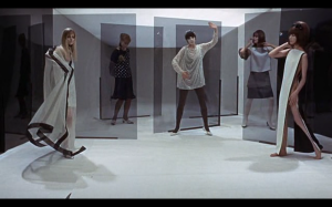 A roomful of models pose in a still from the film.