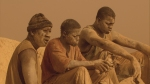 Three gold miners rest after a day at work in a still from the film.