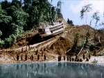 A band of native tribesmen haul the boat up a hill in a still from the film.