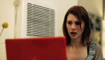 Julie McNiven looks horrified at something on a laptop screen in a still from the film.