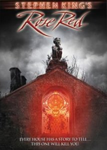 A red, glowing rose illuminates the doorway of the haunted house on the DVD cover.