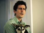 Will, cuddling his dog, looks horrified in a still from the film.