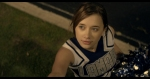 Emily, in a cheerleader outfit, looks pensive in a still from the film.