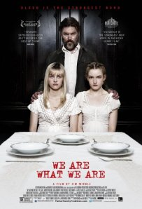 Papa stands behind the two girls, who are seated at the table, on the movie's poster.