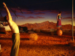 Two characters strike odd poses in a still from the film.