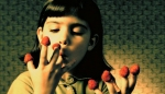 A young Amélie eats raspberries off her fingers in a still from the film.