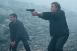 The police advance through the fog, at the ready, in a still from the film.