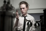 Caleb Landry Jones ponders a vial of bootleg disease in a still from the film.