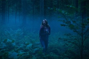 Sara (Dormer) wanders through the forest at night in a still from the film.