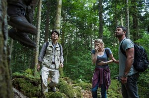Michi, Sara, and Aiden stand at the base of a tree, looking up at a hanging victim in a still form the film.