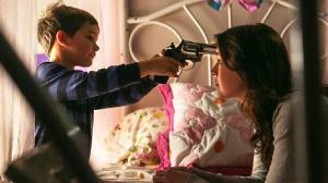 Christopher (Michael Thelin) holds a cocked pistol to Emelie's head in a still from the film.